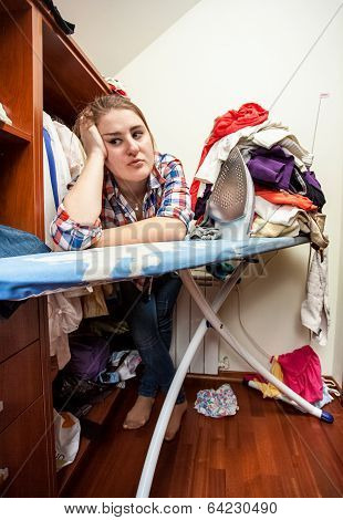 Depressed Housewife Leaning Against Ironing Board