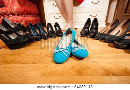 Blue Ballet Flats Standing Among Black High Heel Shoes
