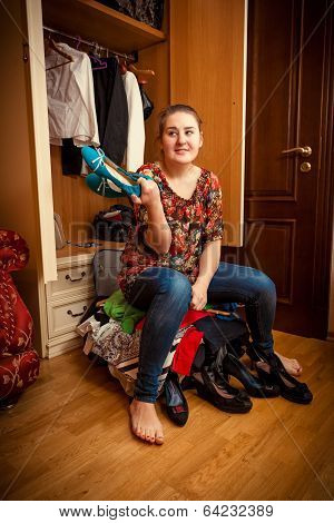 Woman Sitting On Overfilled Suitcase And Holding Shoe