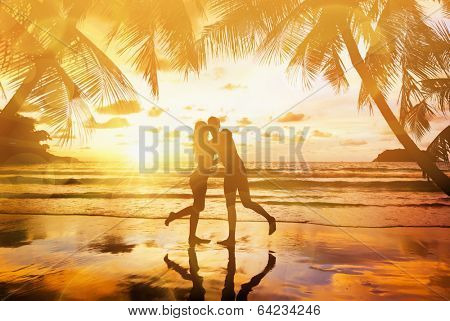 Young couple enjoying the sunset on the beach