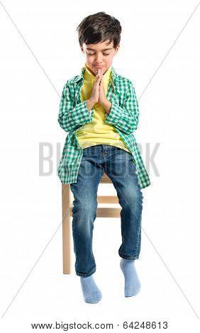 Brunette Boy Pleading On Wooden Chair Over White Background