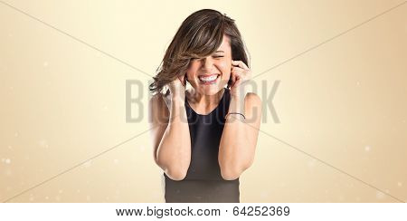 Young Pretty Woman Covering Her Ears Over Ocher Background