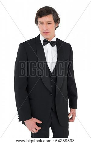 Anxious groom in tuxedo looking down over white background