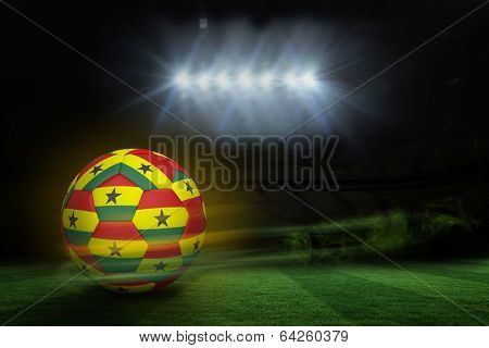 Football in ghana colours against football pitch under spotlights
