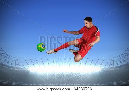 Fit football player jumping and kicking against large football stadium with spotlights under bright blue