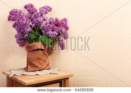Beautiful lilac flowers in paper bag on wooden table near wall