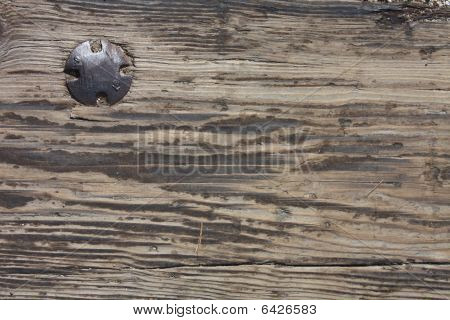 Old weathered plank with old bolt in it