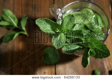Mint in glass jar on wooden background