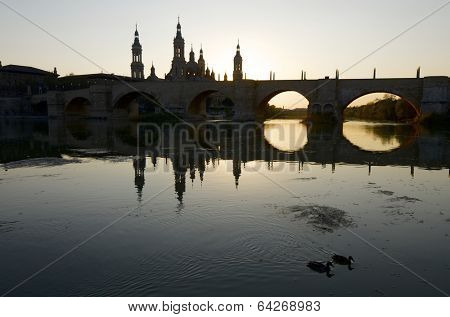 View of the  basilica of the Virgen del Pilar and Ebro river, right is located the medieval bridge known as the Stone Bridge and left the tower of the Cathedral of La Seo, Zaragoza, Aragon, Spain