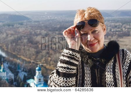 Portrait Of A Mature Woman, Slightly Lifting Sunglasses