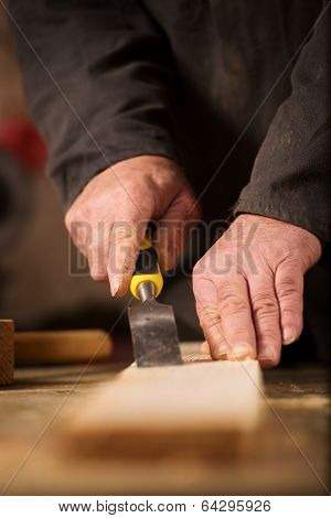 Carpenter Using A Chisel On A Plank Of Wood