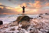 stock photo of glorify  - Teen boy stands on a rock among turbulent ocean seas and fast flowing water at sunrise - JPG