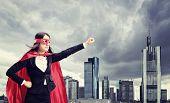 stock photo of superwoman  - Female superhero standing in front of a dark city  - JPG