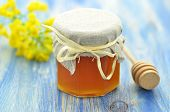 stock photo of rape  - jar of delicious honey in a jar with rapeseed flowers and honey dipper