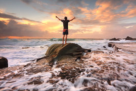 pic of sea life  - Teen boy stands on a rock among turbulent ocean seas and fast flowing water at sunrise - JPG