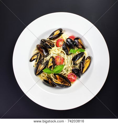 Italian Pasta With Gourmet Shellfish, Cherry Tomato And Herbs For A Tasty Seafood Meal Over Black Ba
