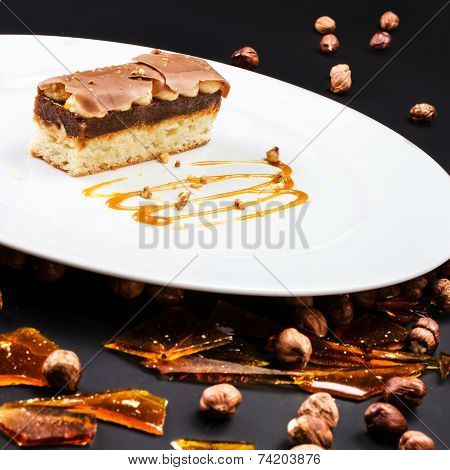 Chocolate Layer Cake With Caramel, Nuts And Chocolate On White Plate Over Black Background, Studio S