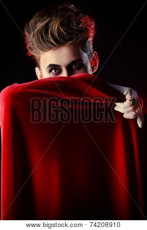 Handsome vampire hiding his face behind his cloak. Halloween. Dracula costume.