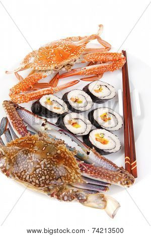 Japanese traditional Cuisine - Roll with Cucumber , Cream Cheese with raw Tuna and Salmon inside. on black dish with red and blue crabs .