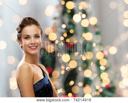 people, holidays and glamour concept - smiling woman in evening dress over christmas tree lights background