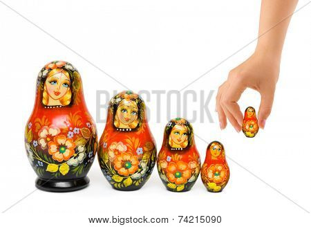 Hand and russian toy matrioska isolated on white background