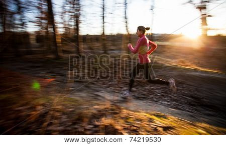 Young woman running outdoors in a city park on a cold fall/winter day (motion blurred image)