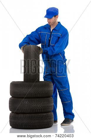 young car mechanic changing car tires on white background