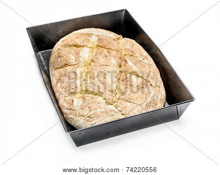 Loaf of home baked bread in baking tin over white background