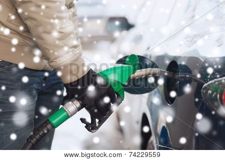 transportation, tanking, people and vehicle concept - close up of man with fuel hose nozzle tanking car