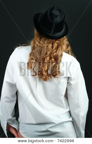 Girl in white shirt and black hat with long blond curly hair