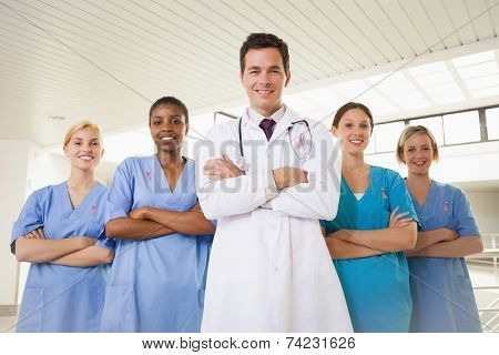 Smiling doctor and nurses with arms crossed wearing breast cancer awareness ribbon