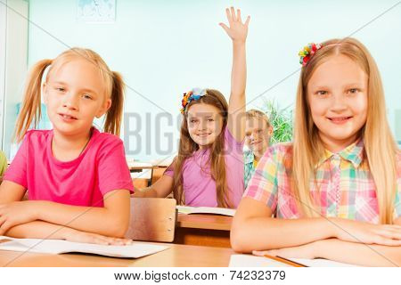 Smiling girl holds arm up behind two girls