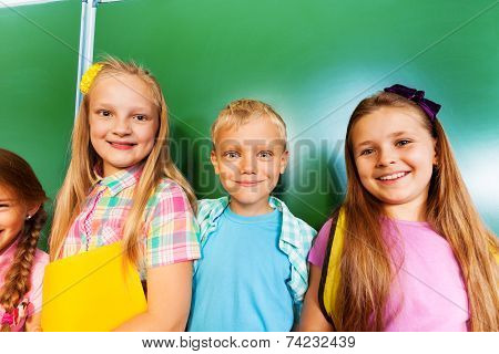 Three children stand together near blackboard