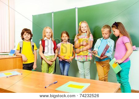 Six children stand in row near blackboard