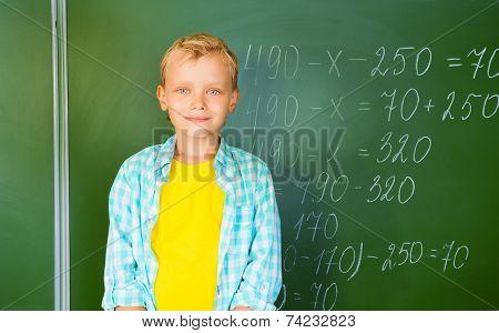 Boy in bright T-shirt stands near blackboard