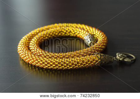 Necklace From Transparent Yellow Beads On A Dark Wooden Surface