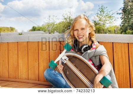 Blond smiling girl with headphones and  skateboard