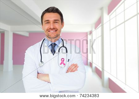 Handsome young doctor with arms crossed against modern white and pink room with window