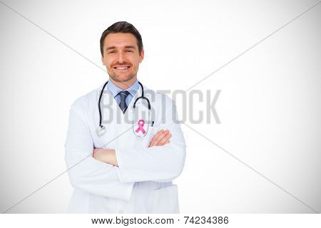 Handsome young doctor with arms crossed against white background with vignette