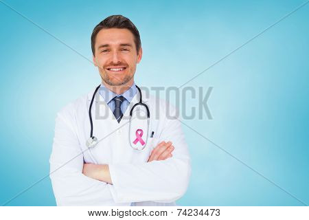 Handsome young doctor with arms crossed against blue vignette
