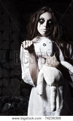 Horror Style Shot: Strange Crazy Girl With Moppet Doll And Needle In Hands