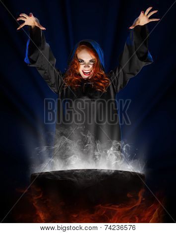 Young witch with cauldron on blue light background