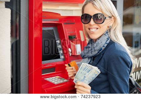 Woman showing cash after withdrawal from ATM