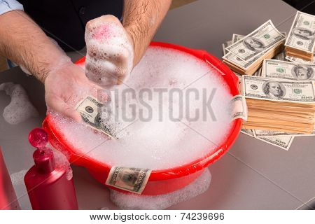 Hands are washing dollars banknotes in foam