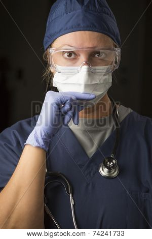 Concerned Female Doctor or Nurse Wearing Protective Facial Wear and Surgical Gloves.