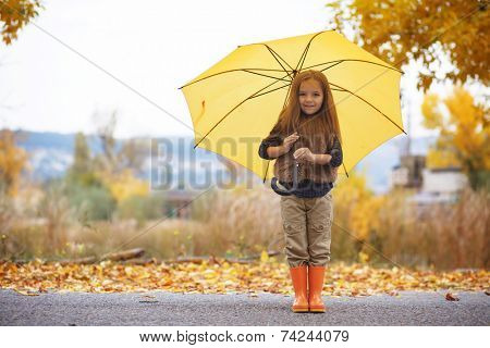 Little child walking with umbrella in the rain in fall park