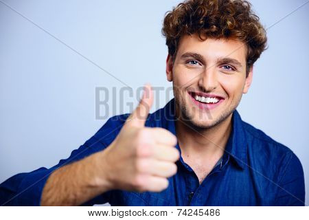 Happy man giving thumbs up sign on blue background