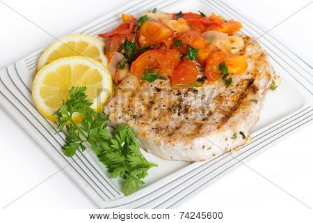 Marlin steak cooked on a plate with tomato salsa, lemon and parsley seen from the side