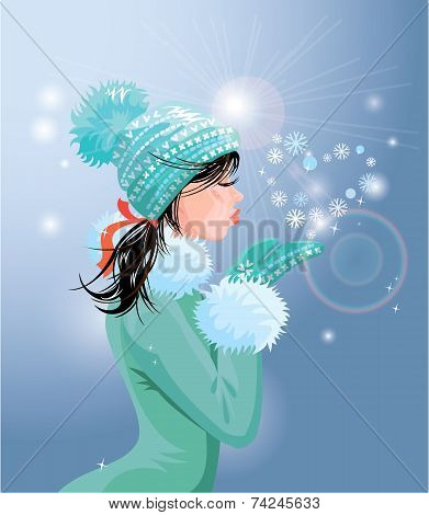 Beautiful Brunette Girl With Warm Blue Winter Hat Is Blowing Snow From Her Hands (snowflakes In Hear