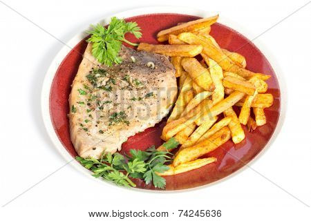 Swordfish steak cooked on a plate with french fries and a parsley and garlic butter sauce